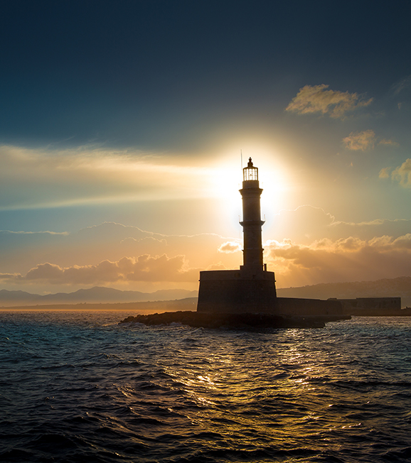 A Lighthouse on the sea against a sunset